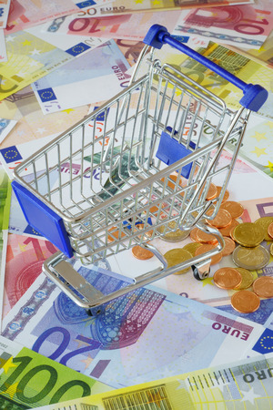 sparingly: Blue small shopping cart on a background made of Euro banknotes and coins