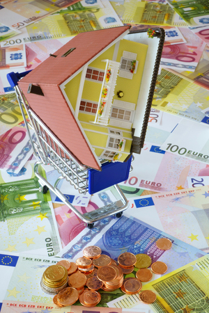 home ownership: Model of a Home Ownership in a shopping cart on a background made of Euro banknotes and coins
