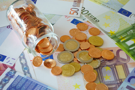 household money: Small glass bottle with coins on a background with Euro banknotes