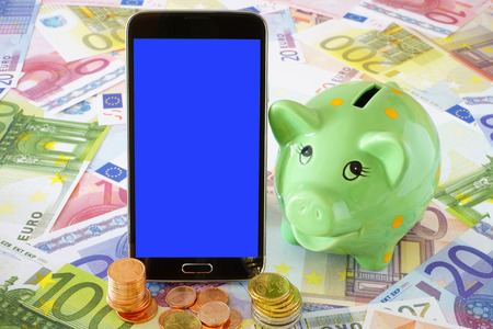 sparingly: Black smart phone with blue blank touchscreen and a green Piggy Bank on a background of Euro banknotes and coins Stock Photo