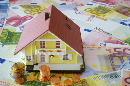 home ownership: Model of a Home Ownership on a background made of Euro banknotes und coins
