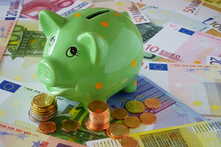 sparingly: Green Piggy Bank on a background made of Euro banknotes und coins