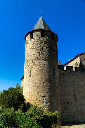 Large round tower with battlements and fortress wall in the historic fortress Carcassonne