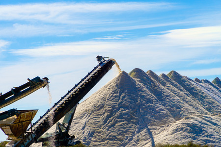 Salt production in the Saline Saint-Martin in Gruissan. With excavator and transportation belt conveyor, sea salt is transported on salt hills. Stock Photo