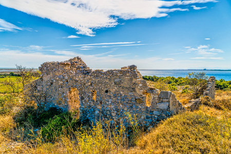 View of an old dilapidated natural stone house in the countryside from the small French village of Gruissan in southern France in the background is the Mediterranean SeaHintergrund ist das Mittelmeer