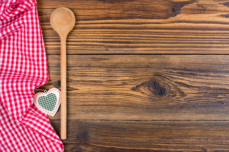 A old wooden cooking spoon and small decoration heart lies on a rustic wooden background with a red white checkered cloth on the left side