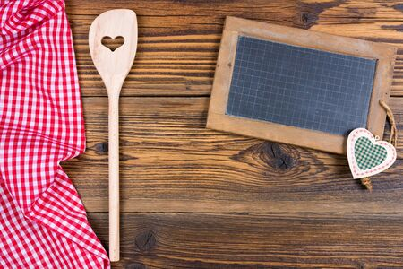 An old slate blackboard and a wooden cooking spoon on rustic wood background on the left side lies a red white checkered cloth