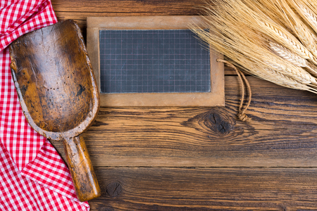 An old slate blackboard, a very old flour scoop and grain ears lie on a rustic wood background with a red white checkered tablecloth with copy space