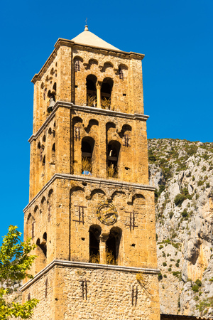Closeup of the bell tower of the old parish church Notre-Dame-de-lAssomption in the small historic mountain village Moustiers-Sainte-Marie in southern France Stock Photo