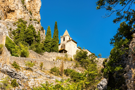 View up to the old chapel Notre Dame de Beauvoir at the foot of the historic mountain village Moustiers-Sainte-Marie on a rocky plateau in southern France in the summer in front of a bright blue sky