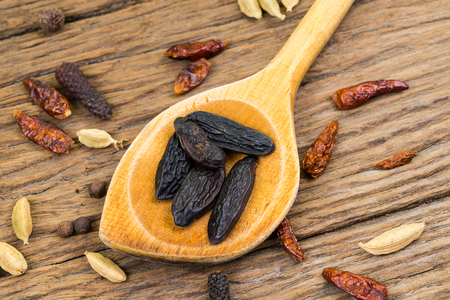 Closeup of whole tonka beans on an old wooden wooden spoon on rustic wood background with copy space 版權商用圖片