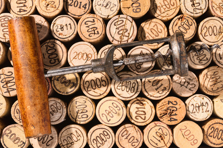 Old corkscrew in retro look lies on a background of many vintage corks Archivio Fotografico