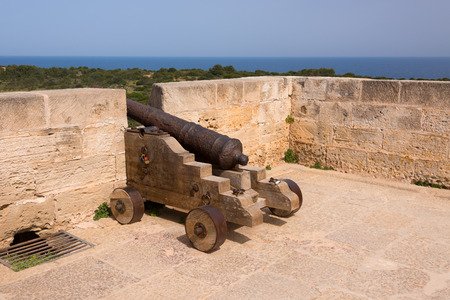 Old antique iron cannon on the old defence tower of Punta de N'Amer near Sa Coma, on the Spanish Balearic Mediterranean island of Mallorca