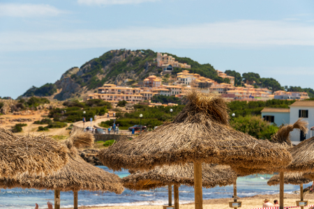 View over straw parasols on the beach of Cala Agulla to houses on the hills of Cala Radjada on the Spanish holiday island Mallorca Banco de Imagens