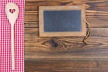 An old slate board and a wooden spoon with a heart-shaped cutout lie on a red and white chequered cloth on a rustic wood background with text space for your own design.