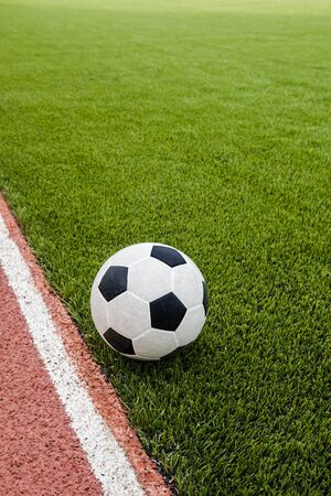 The football is on the artificial grass soccer field in the stadium. Stock Photo