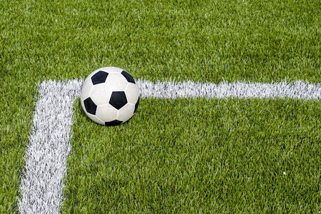 The soccer football on the white line in the artificial green grass field Stock Photo