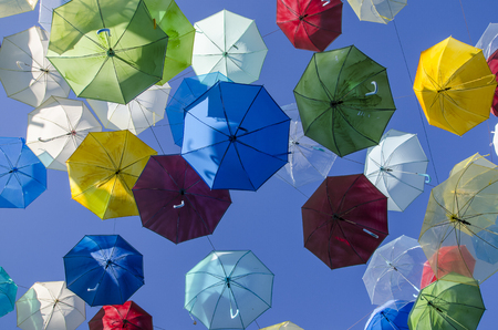 The many colorful umbrellas on bule sky as background, ants eyes view Banco de Imagens