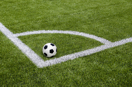 The soccer football in the corner on the artificial green grass field Stock Photo