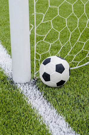 pasto sintetico: The soccer football with the net on the artificial green grass soccer field  Foto de archivo