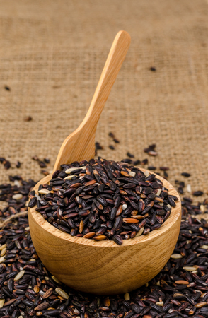 The black rice with spoon in the bowl on the hessian sack bag