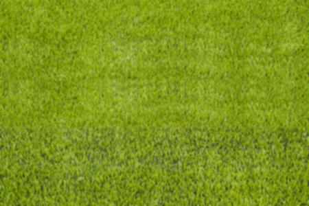 The blur of artificial green grass soccer field for backgroud.