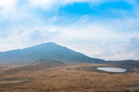View of the volcanic plume of Aso Nakadake and the meadows around it