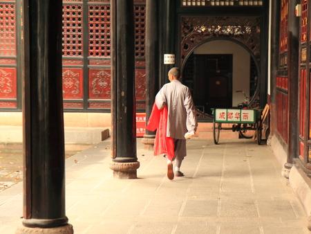 chinese holly: Chengdu China - May 04,2012,Chinese local monk walking along courtyard in Wenshu monastery in Chengdu China Editorial