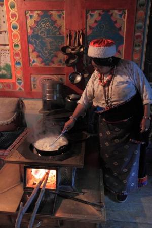Jiuzhaigou China - May 07,2012,Local tibetan lady cooking traditional soup in Jiuzhaigou village China