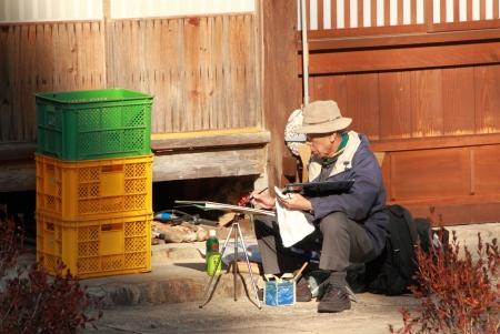 gokayama: Gokayama Japan - November 04, 2012,Japanese man enjoys painting in Gokayama village Toyama Japan Editorial
