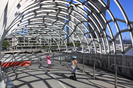 webb: Melbourne Australia- August 10,2013, local kids scootering on artistic design of Webb bridge in Docklands Melbourne Australia Editorial