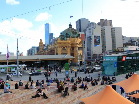 flinders: Melbourne Australia- August 10,2013, Locals and tourists resting and enjoying a sunny day at Federation Square with view of Swanston street and historic Flinders Station in Melbourne Australia Editorial