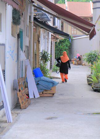 local 27: Singapore, Singapore - 27 May, 2014  Local Muslim woman walks in back street of Arab district Bugis Singapore