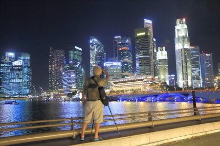 Singapore, Singapore - 28 May, 2014  An elder man takes photos of Singapore skyline in downtown Singapore