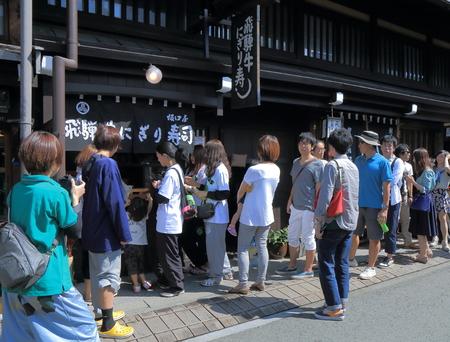 Takayama Japan - 23 september 2014: Mensen staan ??in de rij om beroemde Hida-rundvlees Sushi te kopen in Takayama, Japan Redactioneel