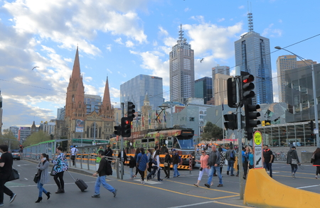 traffic building: Melbourne Australia - September 19, 2015: People cross street in Melbourne downtown Australia.