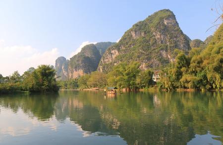 steep: Bamboo rafting karst mountain landscape in Yangshou China