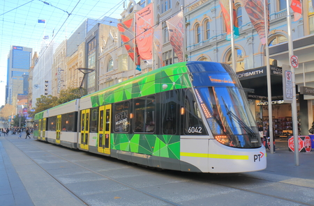 Melbourne Australia - July 7, 2017: Modern tram runs in Melbourne downtown Australia. Melbourne has the largest urban tramway network in the world ahead of St Petersburg. Редакционное