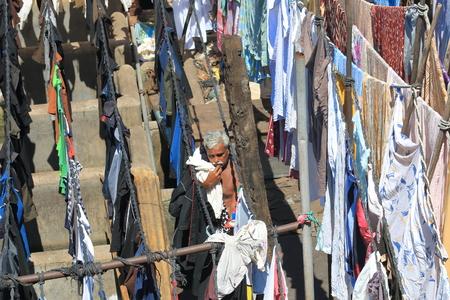 Mumbai India - October 12, 2017: Unidentified man hangs laundry in Dhobi Ghat laundromat Mumbai India.
