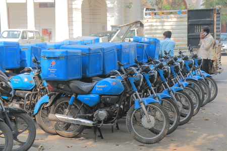 New Delhi India - October 27, 2017: Dominos pizza fast food delivery bikes parked in downtown New Delhi India Editorial