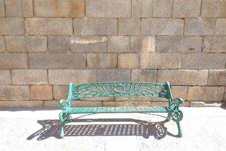 Green steel bench in stone wall background