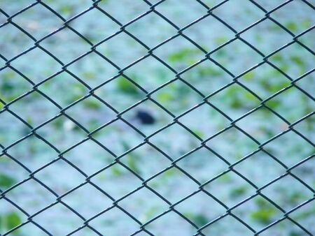 Wire fence closeup with background of Pond