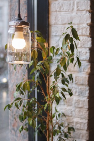 Vintage hand made style lamp on the restaurant window near the plant. Cozy lighting decor for cafe