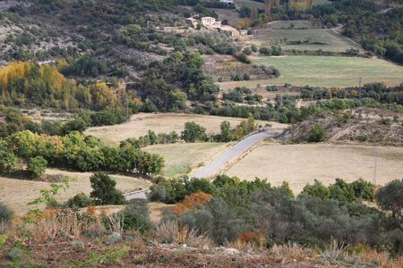 Mountains landscape. Curve of the mountain road in Pyrenees Spain Aragon Campo. Composite autumn landscape Cute road on hillside meadow in mountains. Few fir trees of forest on both sides of the road.