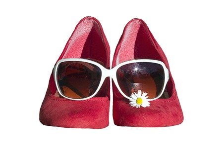 children s feet: Red shoes with glasses and daisies on a white background