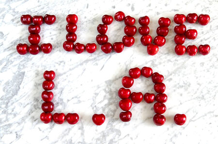 The inscription of cherries I love L A  on the marble table photo