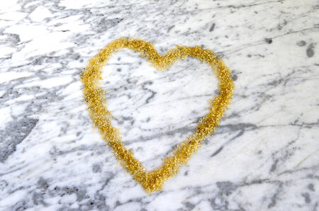 Heart symbol made frown sugar on a marble table photo