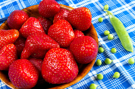 Strawberries with green peas in a wooden bowl photo