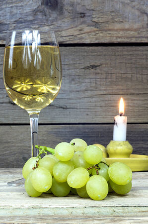 Grape with a glass of wine and candle on old wooden table photo
