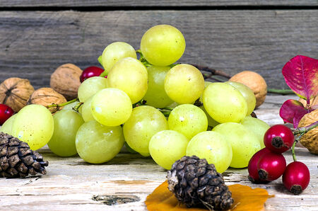 Grapes and walnuts on an old wooden table photo